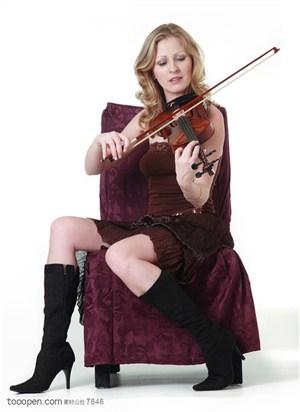 演奏小提琴-坐在椅子上拉小提琴的外国美女